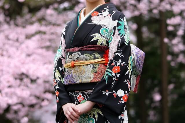 桜の前にいる振袖の女性