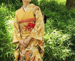 葉っぱの前に立つ着物女性